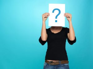 13239832 - beautiful, young woman showing a question mark on a white piece of paper in front of her head, on blue background